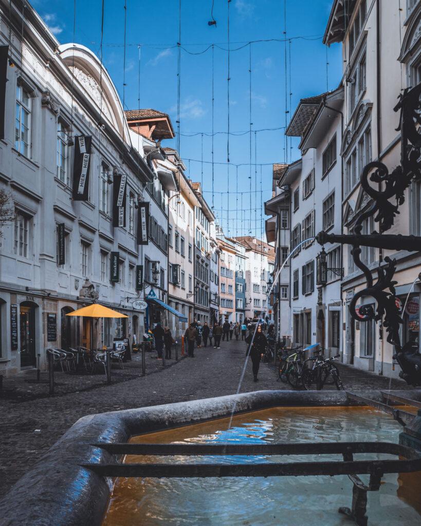 Fonte no Centro Histórico de Zurique, com a rua pedonal de pedras cheia de pessoas. De um lado, embaixo de prédios antigos, vários cafés e restaurantes. Do outro, várias bicicletas estacionadas.