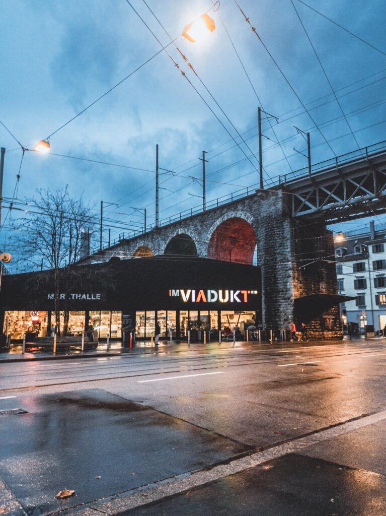 Markthalle Im Viadukt debaixo do viaduto de Zurique, todo iluminado ao anoitecer.