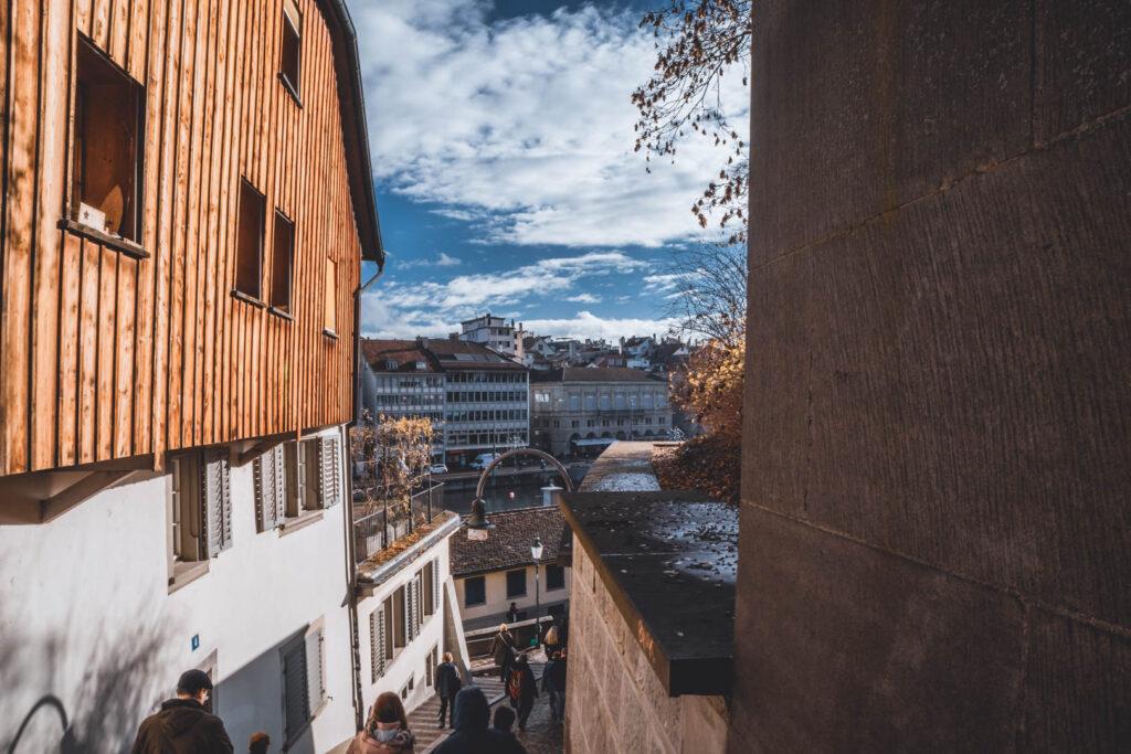 No alto de uma das ruelas de Zurique, próximo ao Lindenhof, com vista para o Limmat. Além disso, várias pessoas passando em uma escadinha lateral que fica embaixo de uma casa de madeira.