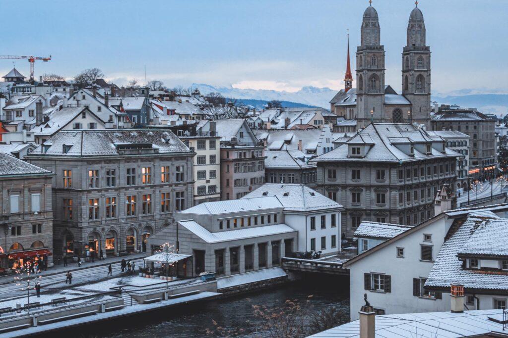 Vista para o Centro Histórico de Zurique ao anoitecer, com as típicas casinhas medievais, vielas estreitas e a Igreja Grossmunster ao fundo, tudo coberto de neve.