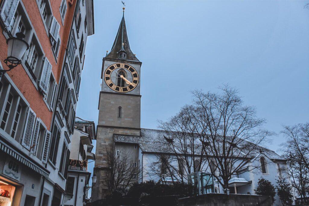 Igreja de São Pedro circundada por árvores já sem folhas. Está localizada na cidade velha de Zurique e é conhecida pela sua enorme torre de relógio, que dá para ser vista em várias partes da cidade.