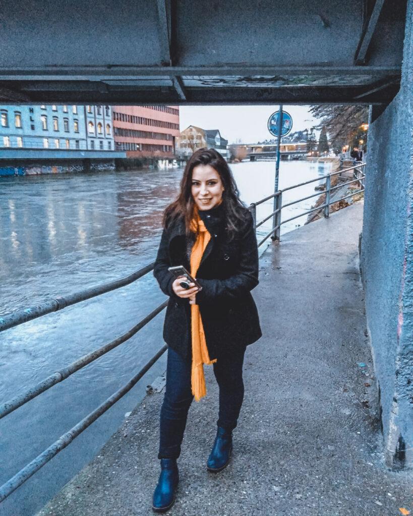 Marjorie sorrindo para a foto enquanto passeia pelas margens do rio Limmat, na área mais alternativa da cidade, a Zurich West