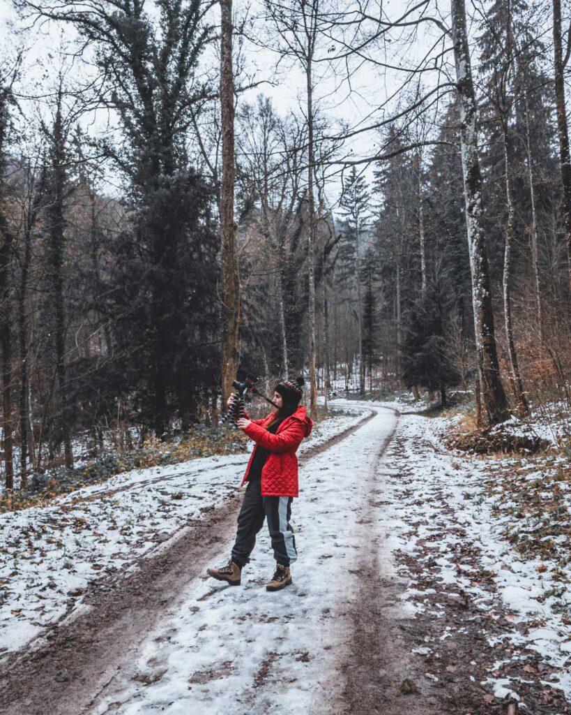 Marjorie em uma trilha para o topo da montanha Uetliberg, que está coberta de neve e árvores em volta.