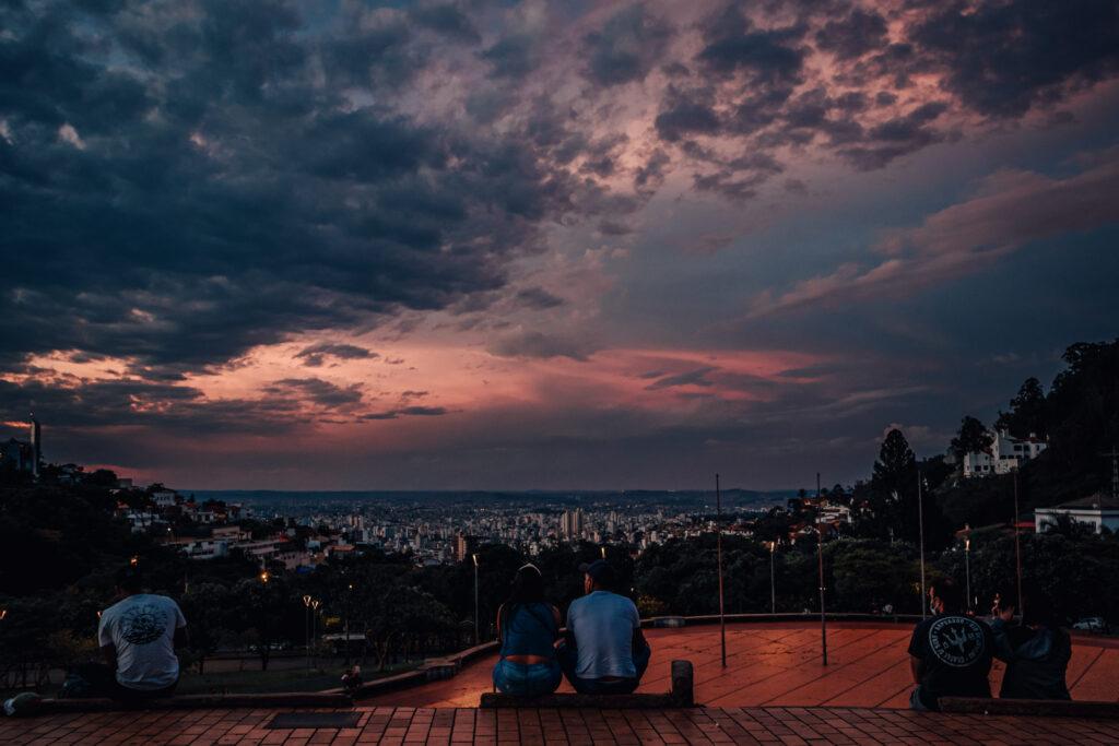 Pessoas sentadas admirando o pôr do sol e a vista para a cidade de Belo Horizonte na Praça do Papa.