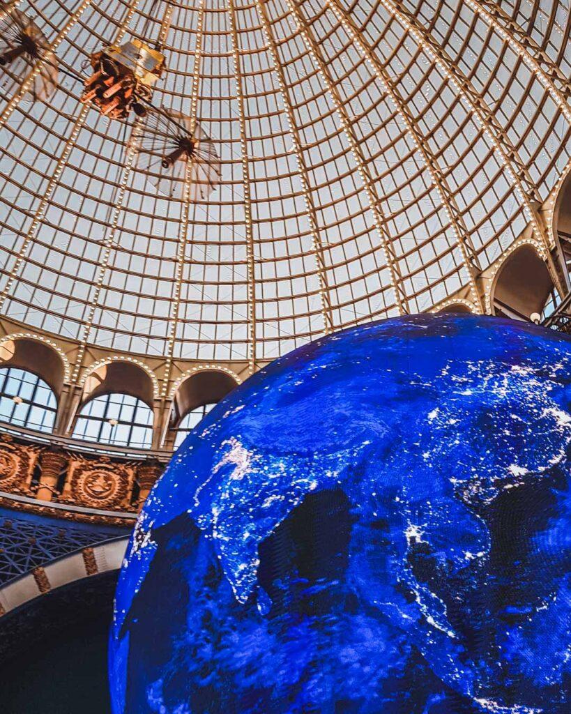 Parte do monumento iluminado do Planeta Terra no interior do Museu do Cosmos, com a cúpula dourada e de vidro em cima.