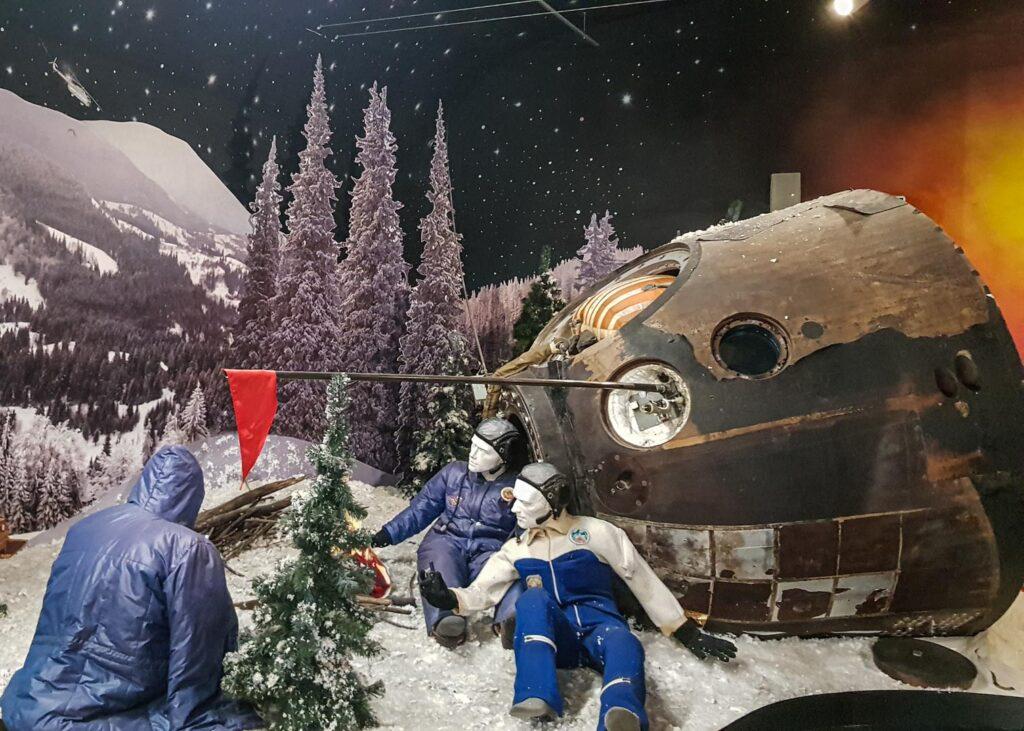 Simulação de um pouso com 3 bonecos e parte de um foguete em um local remoto, com neve e pinheiros, no museu dos Cosmonautas, em Moscou.