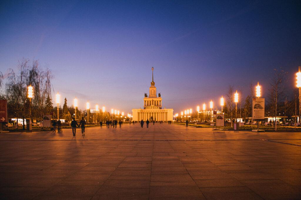 O Pavilhão Central, com a Casa dos Povos da Rússia no final de um um extenso caminho iluminado do VDNKh à noite.