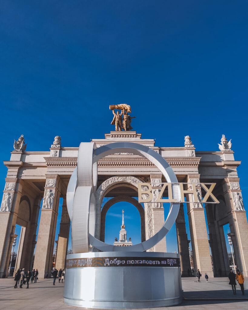 Portão de entrada para o Parque Soviético VDNKh, com o Arco do Triunfo enorme que tem uma estátua no topo, representando um trabalhador e uma camponesa segurando um ramo de trigo.