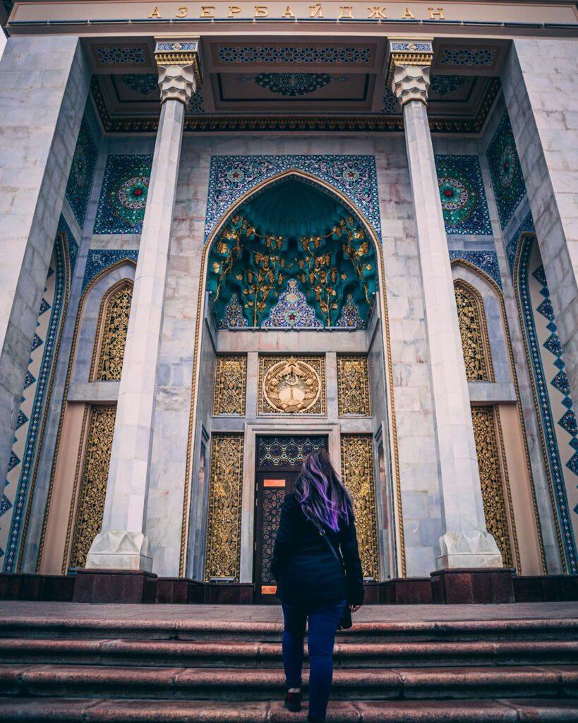 Subindo as escadas até a porta de entrada do edifício no Pavilhão do Azerbaijão, ornado com detalhes dourados e verdes.