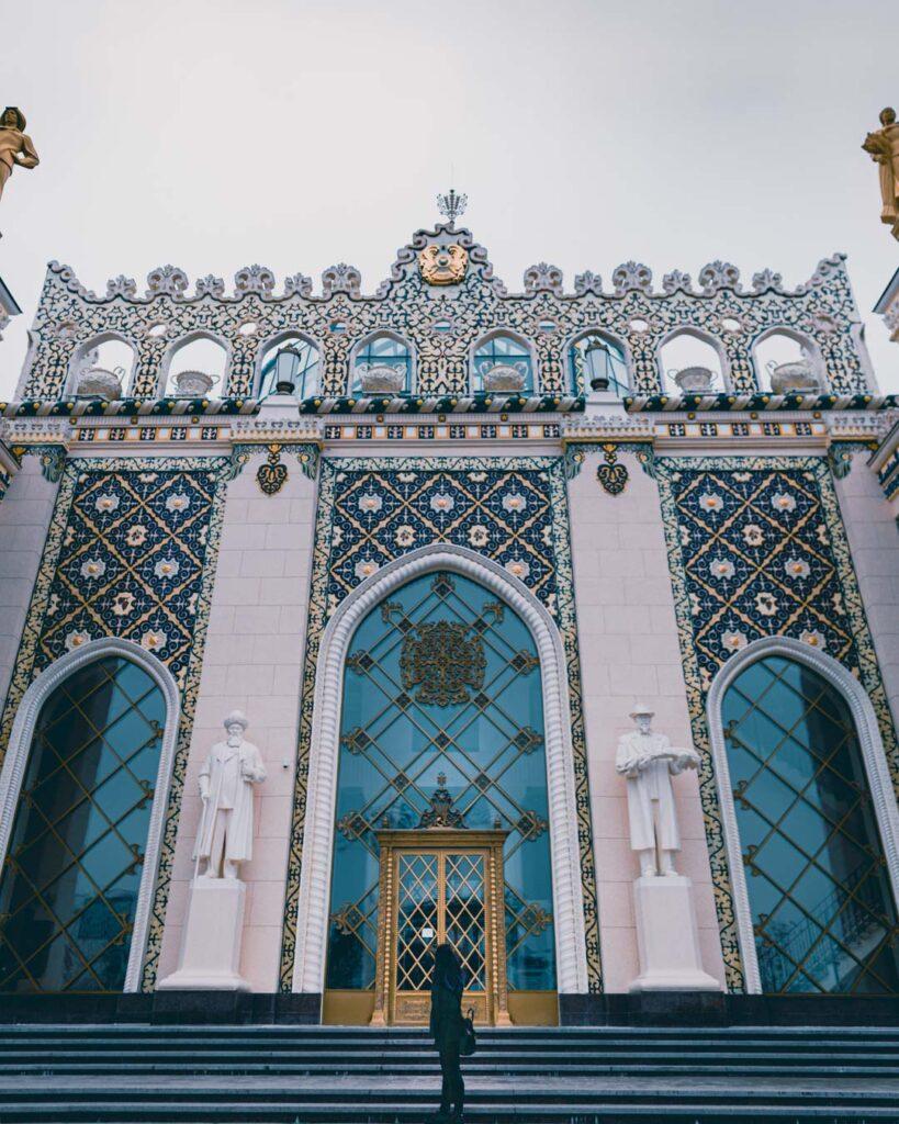 A frente do edifício do Pavilhão que representa o Cazaquistão, com uma construção cheia de azulejos azuis e vidraças enormes.