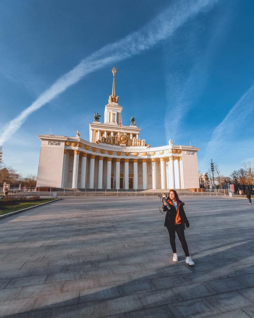 Gravando o vlog de Moscou no Pavilhão Central do VDNKh, com as colunas da Casa dos Povos da Rússia iluminadas pelo sol, ao fundo.