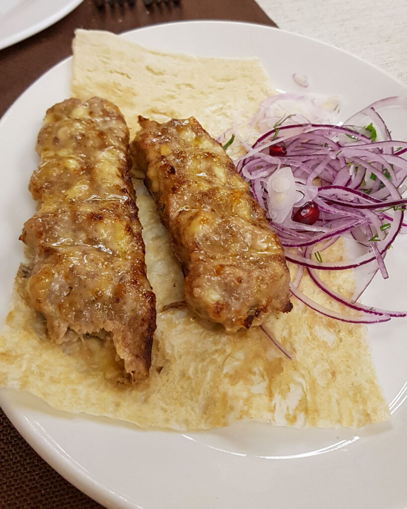 Comida armena com cebola, pão e duas carnes do Restaurante Ararat, no Pavilhão da Armênia no VDNKh.
