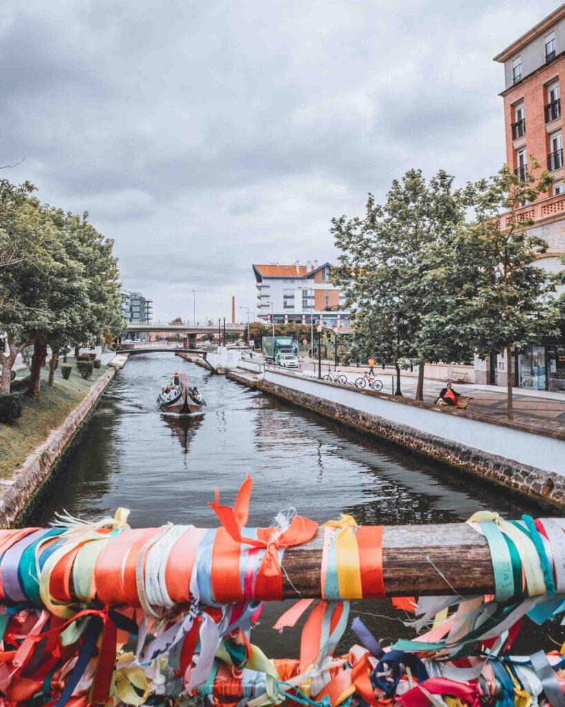 Barco visto da Ponte Laços de Amizade, com parte de seus laços coloridos. cortando as águas do canal Cais do Côjo, com muitas árvores ao redor.