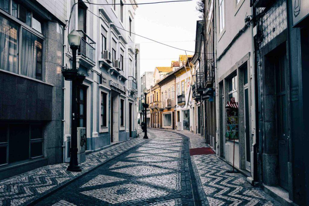 Rua de pedra ladeada por casas cinzas e coloridas em uma viela do Centro Antigo de Aveiro.