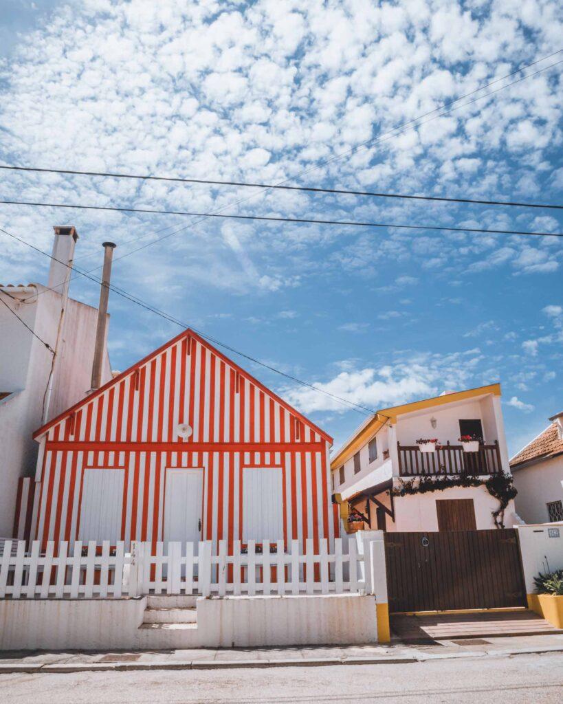 Uma casa listrada de branco e vermelho, mais conhecida como Palheiro, na Costa Nova.