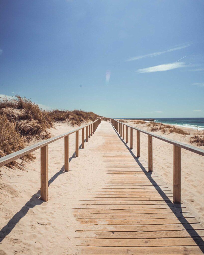 Extenso caminho de madeira em cima da areia na Praia da Costa Nova com o mar ao lado.