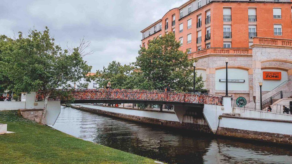 Ponte Laços de Amizade cortando um dos canais da Ria de Aveiro e chamando atenção com os laços coloridos amarrados.