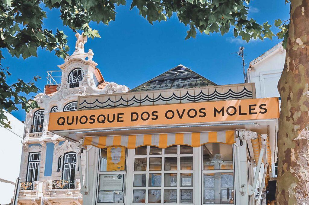 Barraquinha em frente ao Museu da Arte Nova, com detalhes brancos e amarelos na fachada para comprar os doces Ovos Moles.