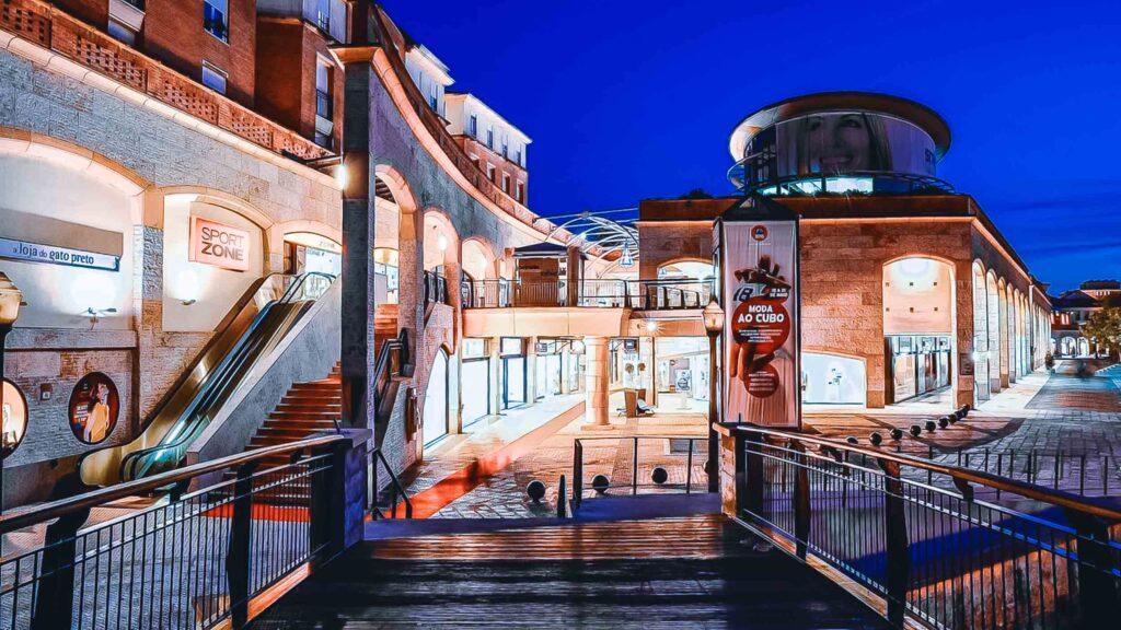 Shopping de Aveiro conhecido por ser um projeto a céu aberto, com escada rolante e várias lojas iluminadas na parte da noite.
