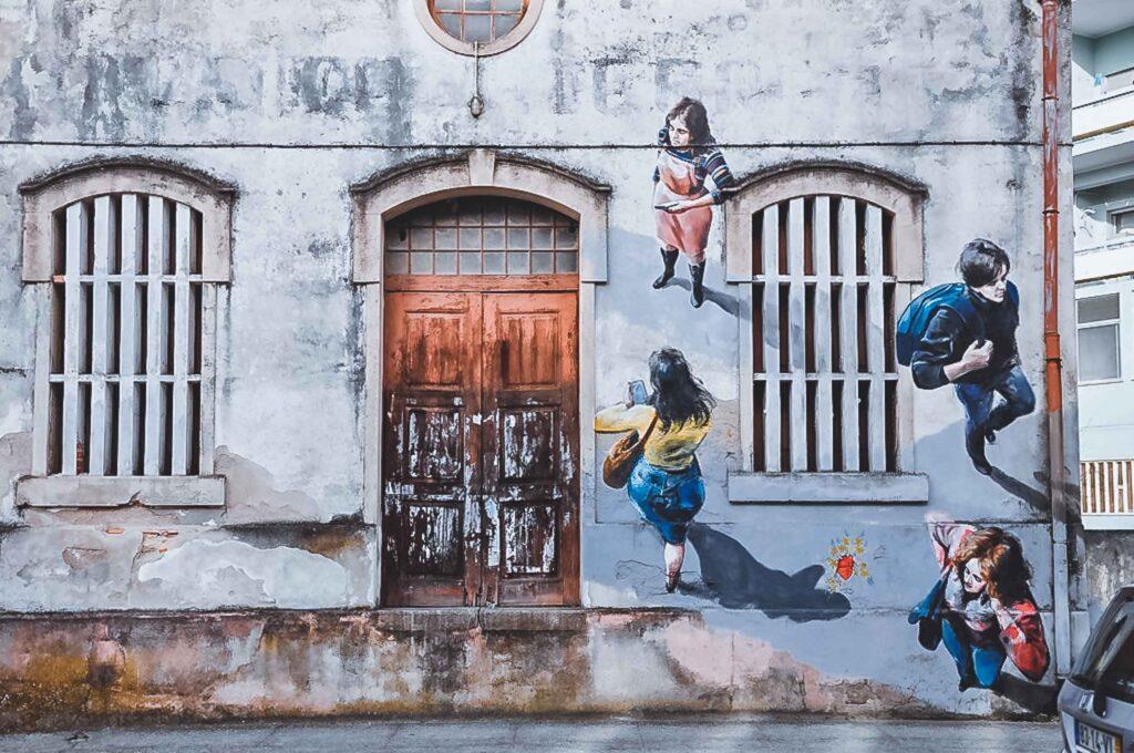 Parede exterior de uma casa em Aveiro grafitada com 4 pessoas diferentes andando.