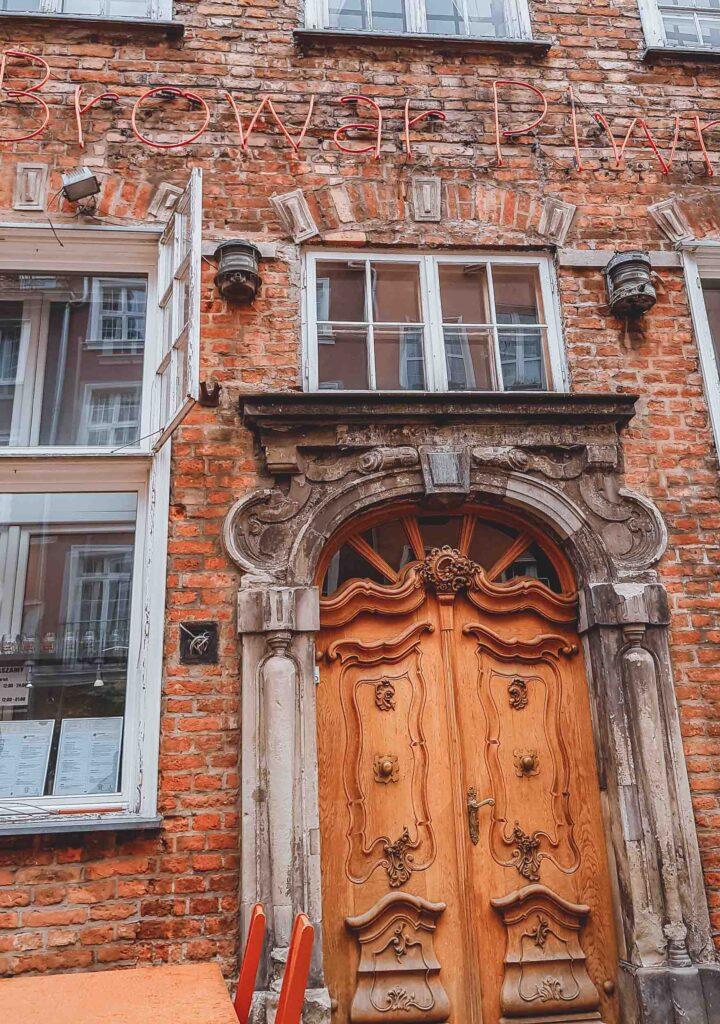 A famosa cervejaria Ulica Piwna, que fica localizada em um edifício de tijolos e porta de madeira.