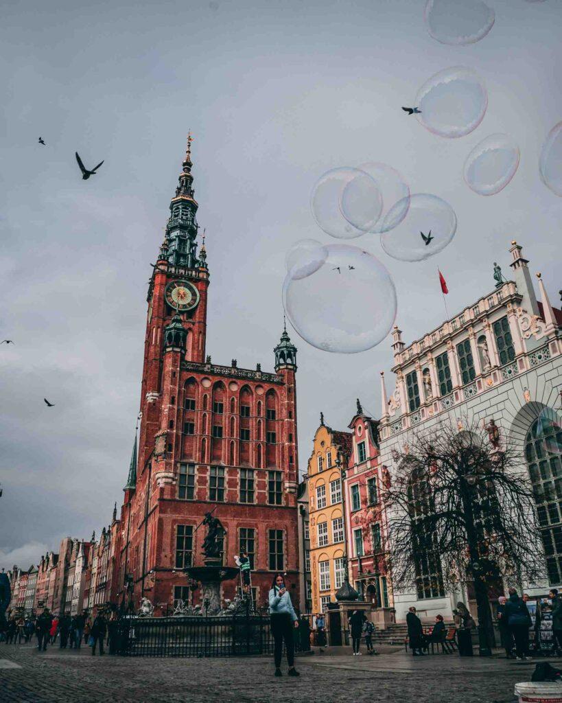 Vista para a Prefeitura de Gdansk, Artus Court e Fonte de Netuno no Long Market, com vários pássaros cortando os céus.