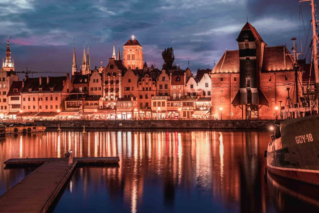 O Guindaste e parte da cidade antiga de Gdansk à noite, com todos os edifícios iluminados na margem do Rio Motlawa.