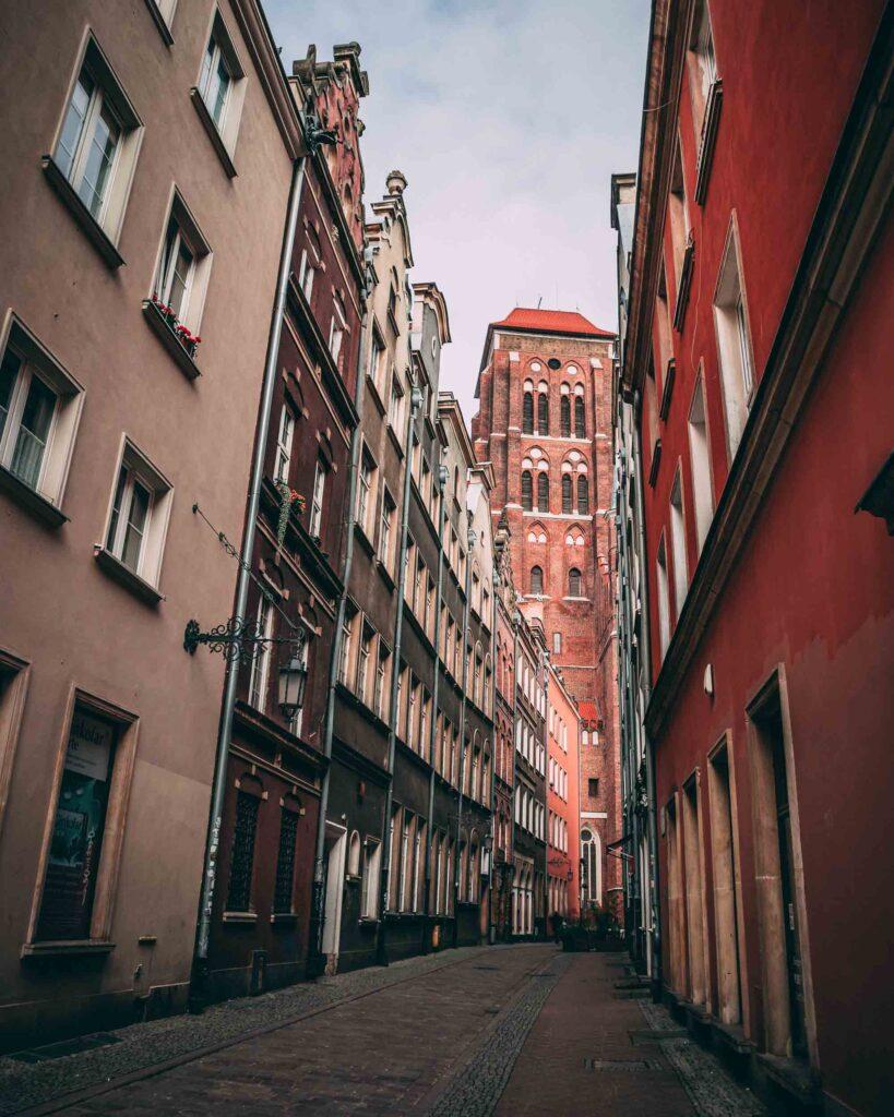 Uma ruela na cidade antiga de Gdansk no meio de edifícios coloridos.