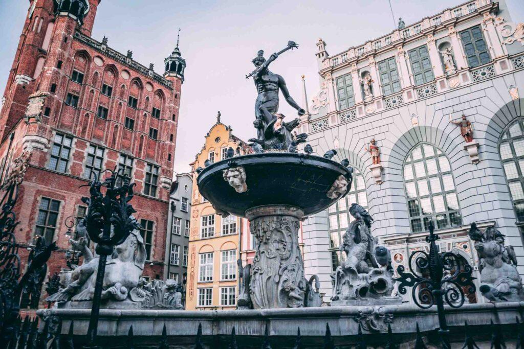 A Fonte de Netuno é um monumento em bronze construído em frente ao Artus Court (edifício de tijolos brancos, detalhes dourados e esculturas), bem ao lado da Prefeitura de Gdansk.