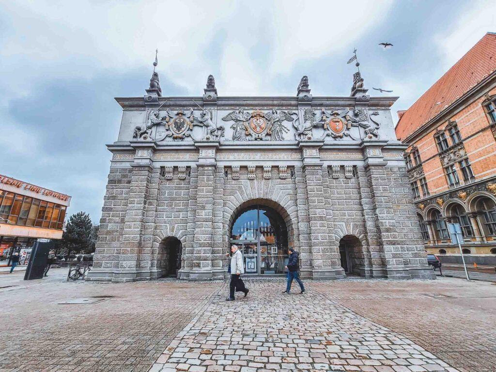 Portão Highland Gate, com tijolos e esculturas em seu topo. Ele dá início ao caminho real pela cidade antiga de Gdansk