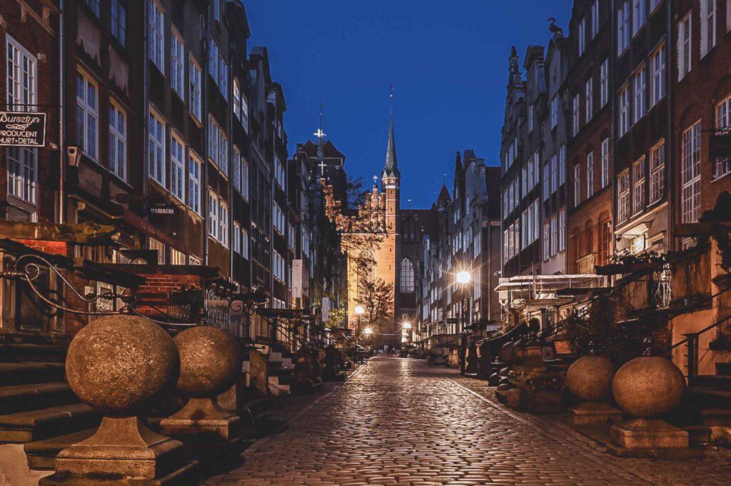 Casas em torno da extensão pedonal e iluminada da Rua Mariacka à noite, com a Igreja de Santa Maria ao fundo, no final do caminho de piso de pedra.