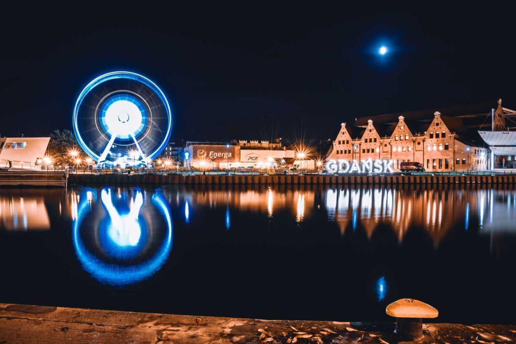 A Roda Gigante e o letreiro de Gdansk iluminados de azul e refletidos nas águas do Rio Motlawa.