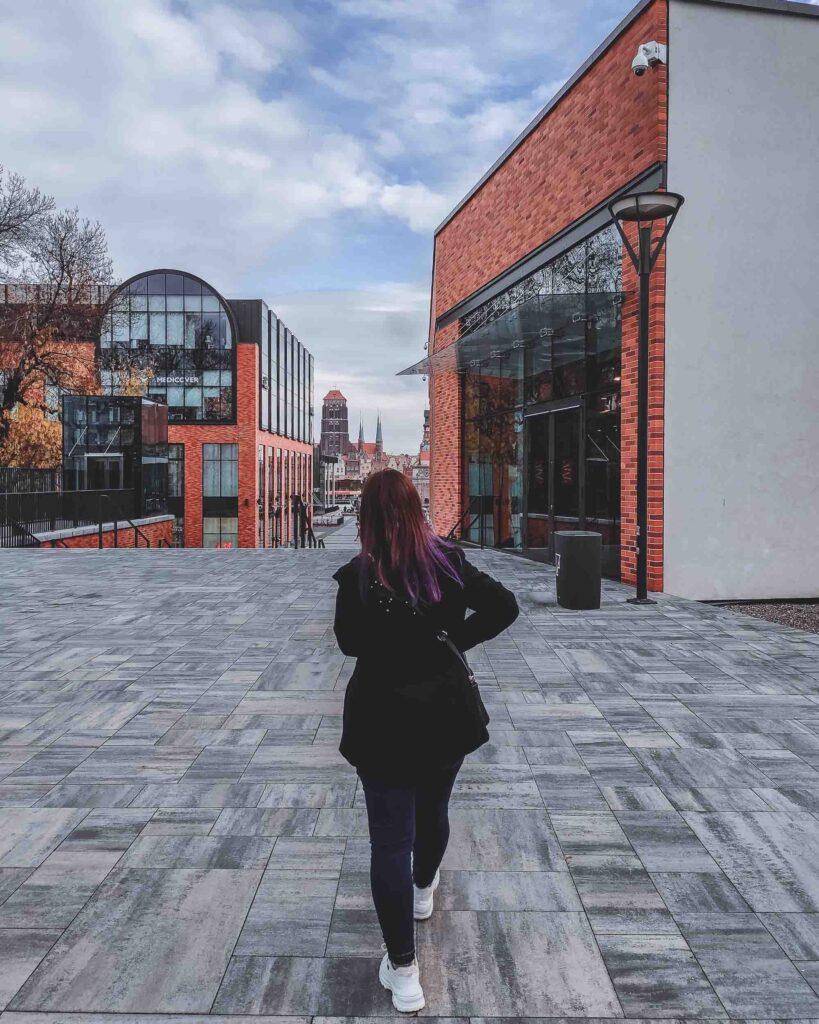 Marjorie andando pela área do inovador Shopping Forum Gdansk, que chama a atenção por ser um edifício cheio de vidraças entre tijolos laranjas.