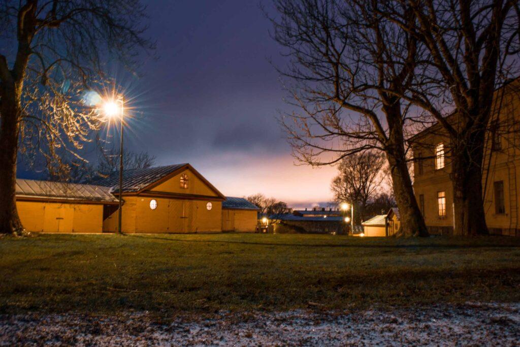 Casas amarelas da área residencial iluminadas por postes de luz em um terreno gramado de Suomenlinna.