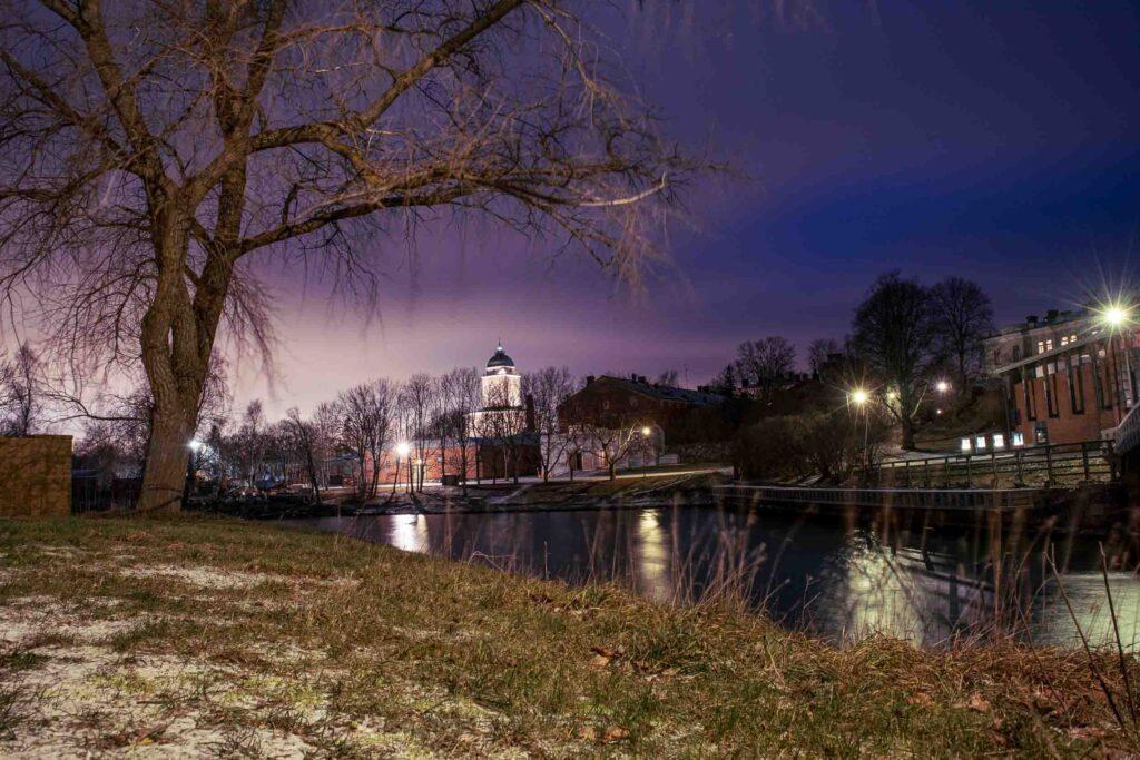 Margem onde está localizada a Igreja iluminada de Suomenlinna com diversas árvores sem folhas, postes acesos e outros edifícios. Está a noite.