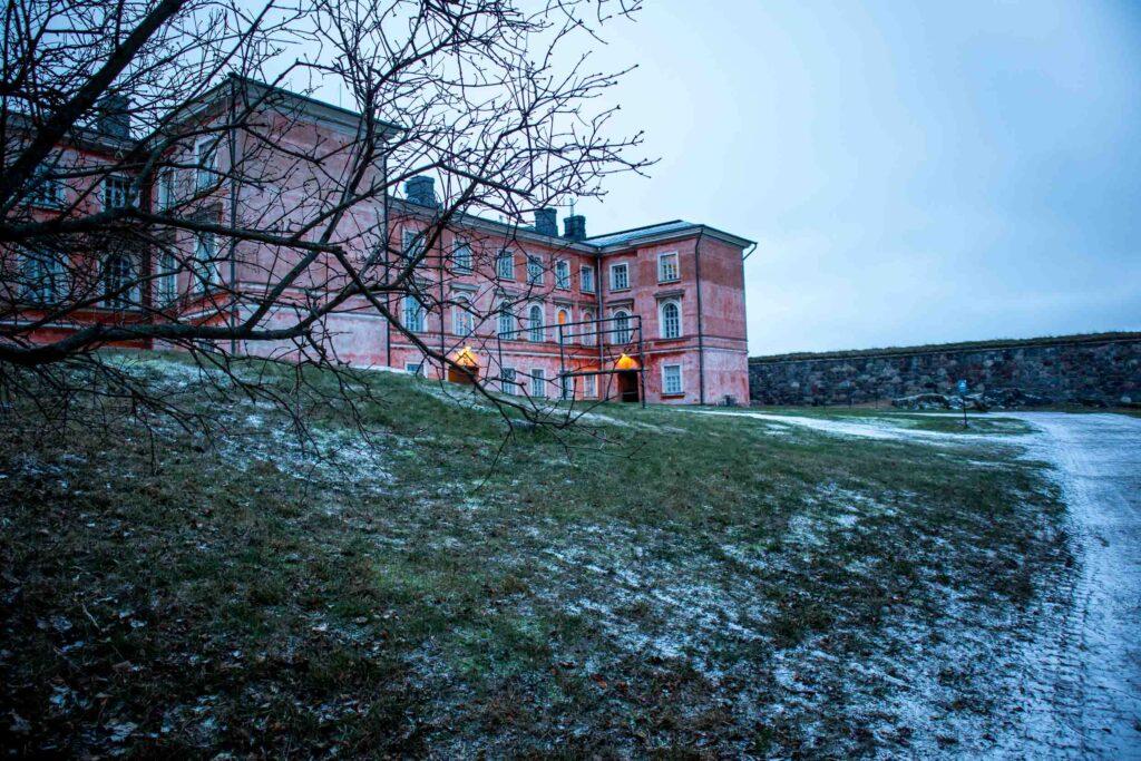 Caminho de gramado coberto de neve até um edifício rosa de três andares com muitas janelas do lado de parte da Fortaleza de pedra de Suomenlinna.