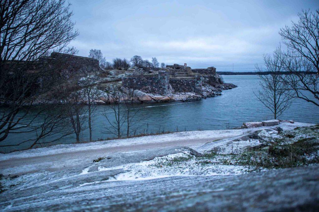 Vista para parte da Fortaleza de pedra de Suomenlinna de uma das margens da ilha. As árvores estão sem folha e o chão coberto de neve.