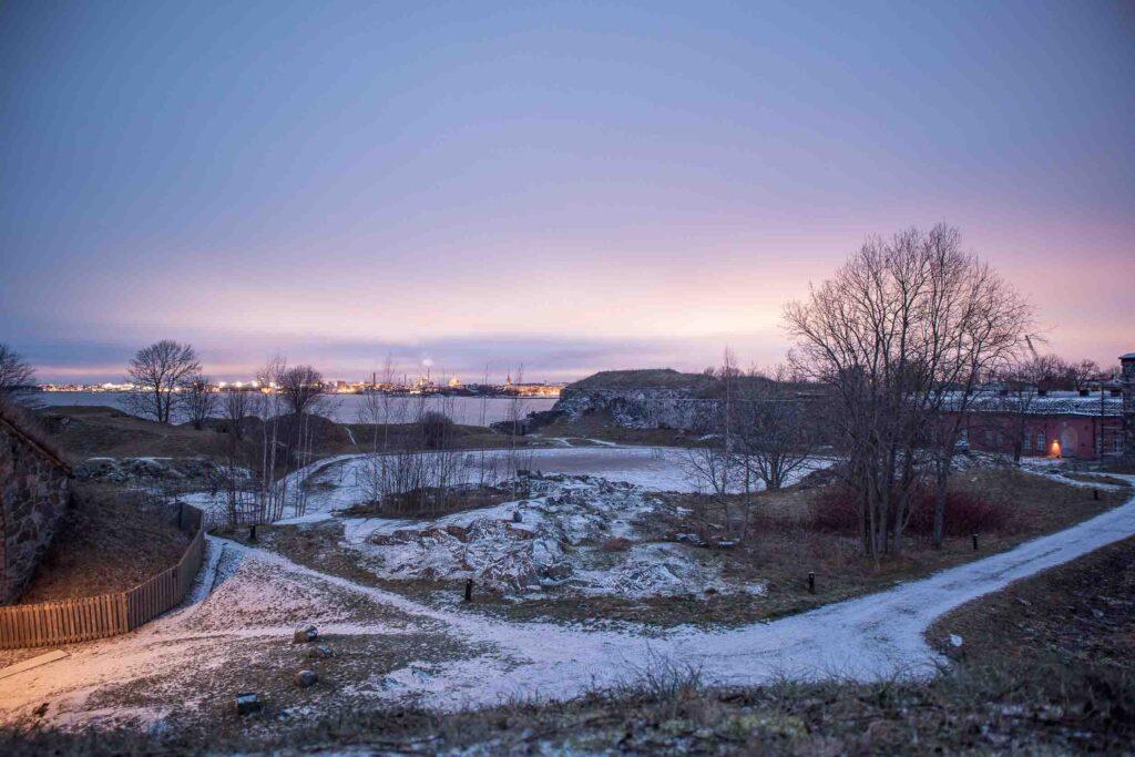 Sol se pondo sob a cidade de Helsinki, vista de longe pela Ilha de Suomenlinna, que está coberta de neve.