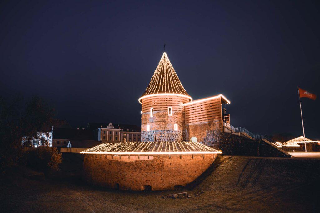 Castelo de Kaunas na parte da noite, todo iluminado com luzinhas e piscas piscas de natal.