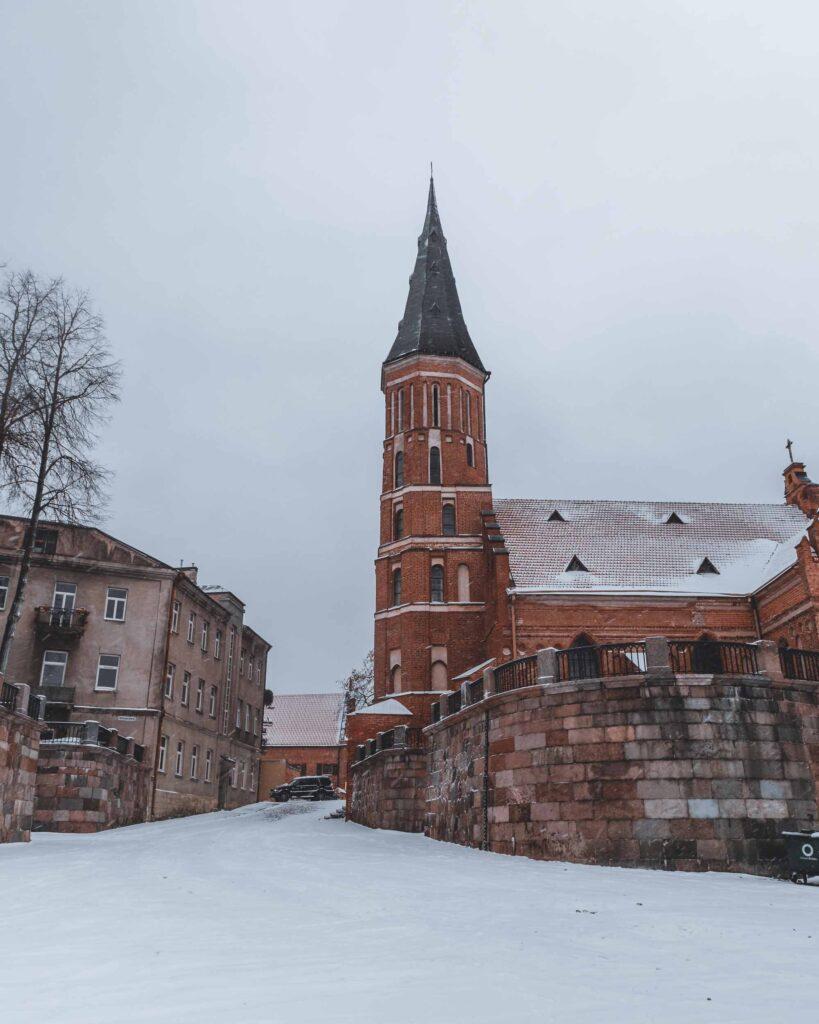 Igreja da Assunção da Virgem Maria ou Grande Igreja de Vytautas coberta de neve. Esse edifício religioso tem uma torre e foi construído em estilo gótico.