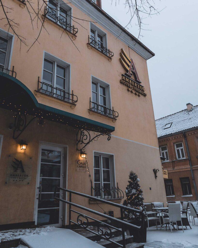 Fachada do Amberton Hotel, com várias janelas e a logo do hotel colada. O lado de fora tem várias mesas e cadeiras, árvore e outras decorações de natal.