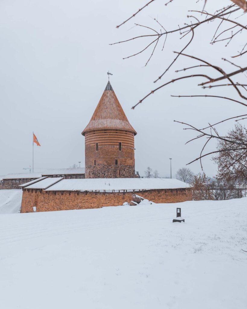 Castelo de Kaunas e parte da fortaleza cobertos de neve em um dia nublado.