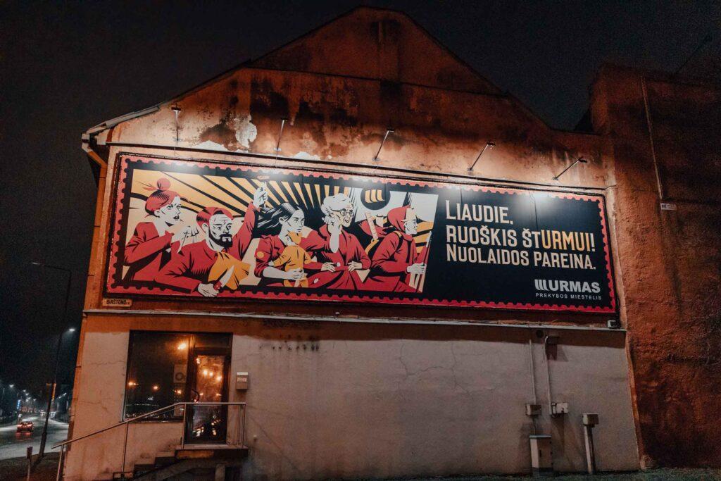 Idioma da Lituânia. Placa iluminada em uma casa de Kaunas, com palavras do idioma lituano.