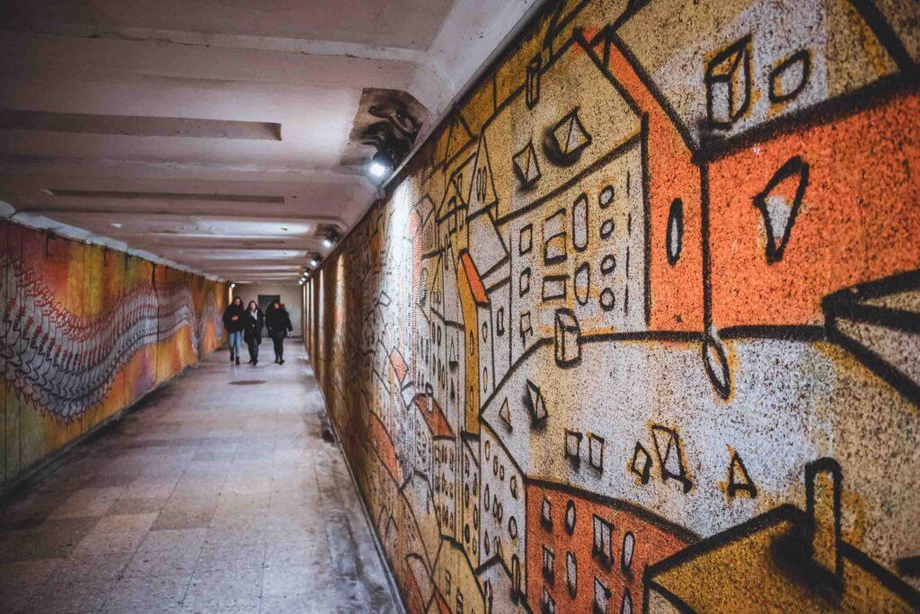 Grafite com várias casas em tons de laranja da arte urbana em Kaunas, localizado na parede de um dos túneis da cidade.