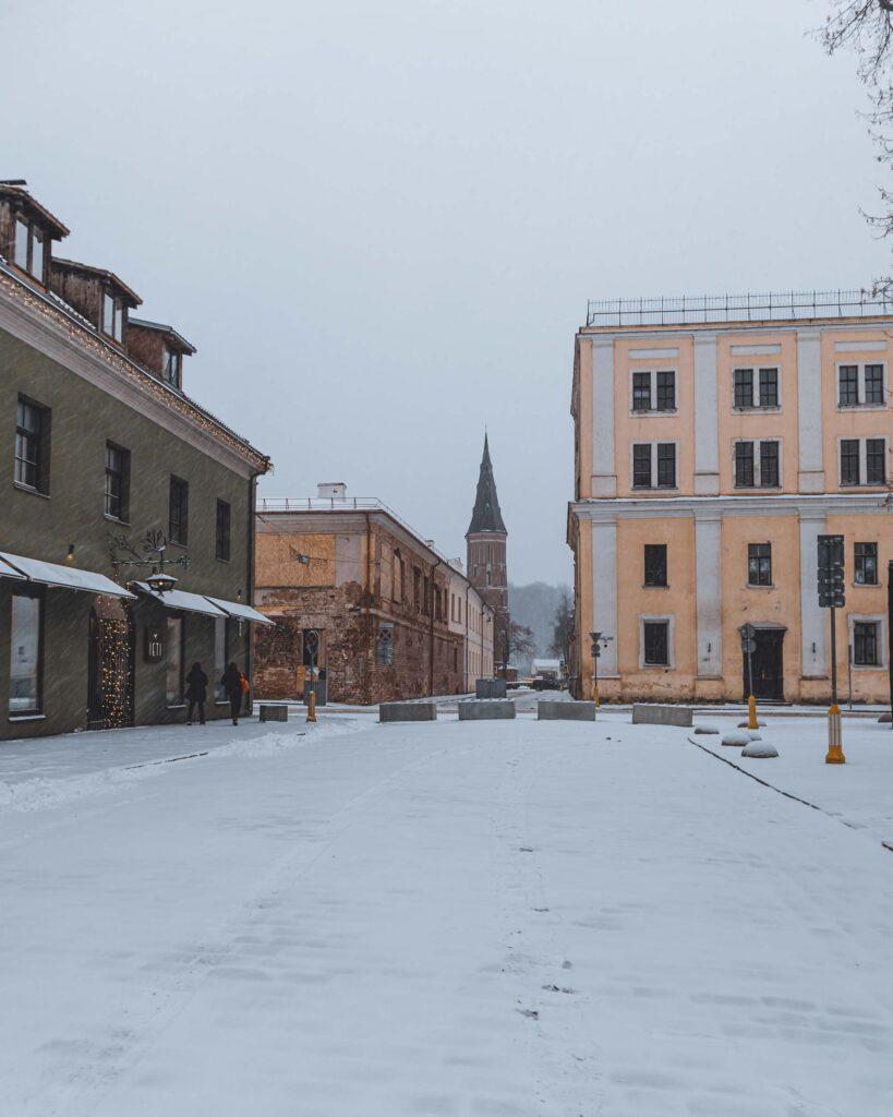 Rua da Cidade Velha de Kaunas coberta de neve e com a torre da Grande Igreja Vytautas no fundo.
