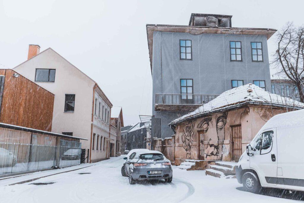 Neve caindo em uma rua de Kaunas, com carros estacionados e uma casa marcada pela Street Art.