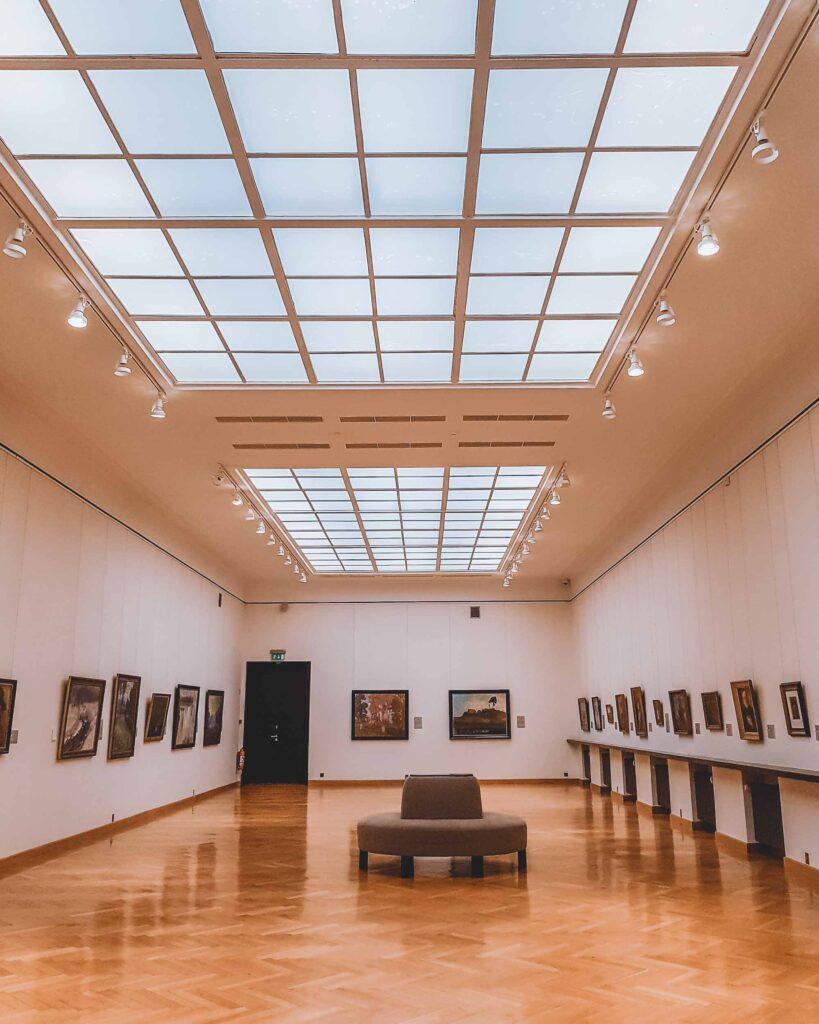 Uma das áreas de exposição do Museu Nacional de Arte Čiurlionis, com uma sala cheia de quadros nas paredes um sofá no centro.