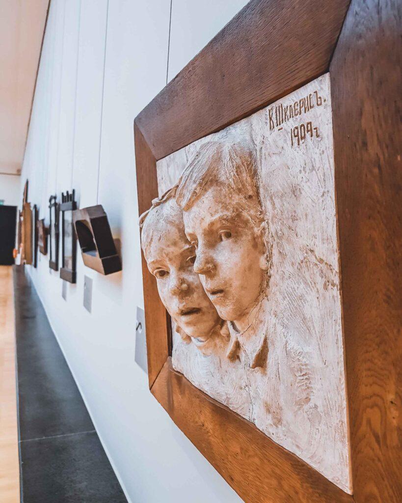 Escultura de duas cabeças saindo para fora do quadro no Museu Čiurlionis.