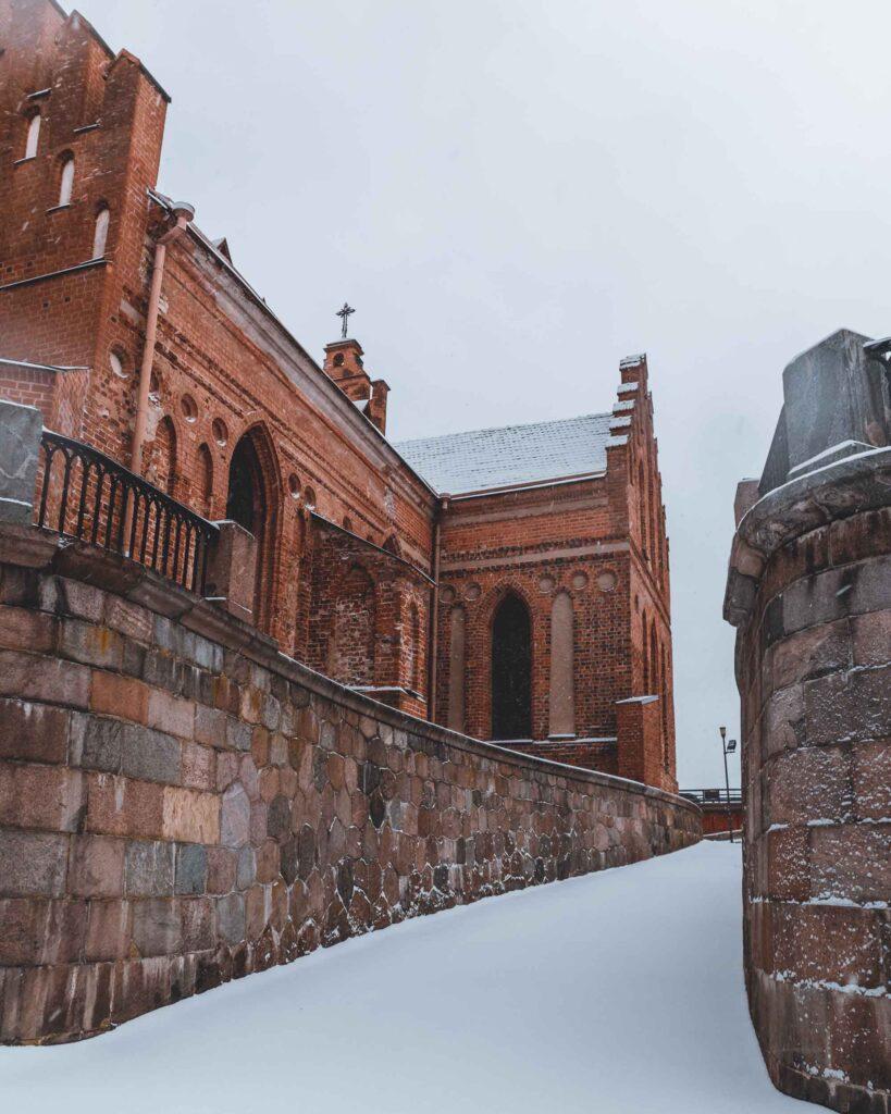 Lateral da igreja gótica de tijolinhos laranjas de Kaunas, a Grande Igreja de Vytautas.