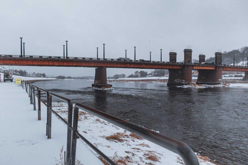 Carros passando pela Ponte Vytautas, que corta o Rio Nemunas. As margens estão cobertas de neve.